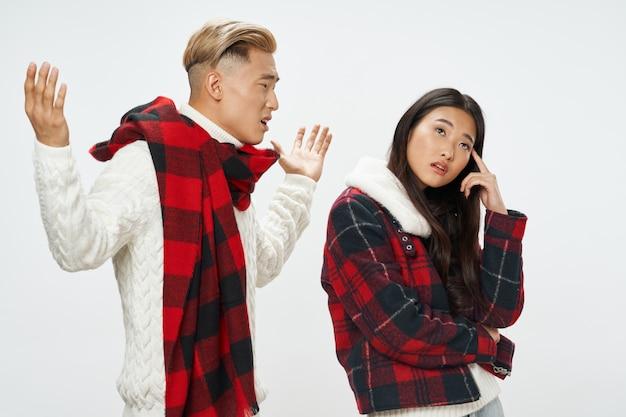 Homem e mulher de aparência asiática com cachecol e jaqueta xadrez Foto Premium