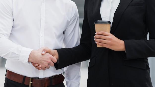 Homem e mulher de negócios, apertando as mãos Foto gratuita
