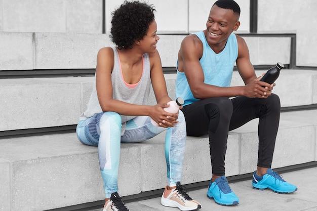 Homem e mulher de pele escura, alegre e motivada sentam-se na escada, olham positivamente um para o outro, seguram garrafas com água, usam roupas esportivas e tênis, discutem sobre competições esportivas. Foto gratuita