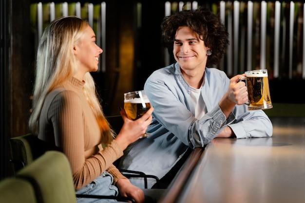 Homem e mulher de tiro médio com canecas de cerveja Foto gratuita