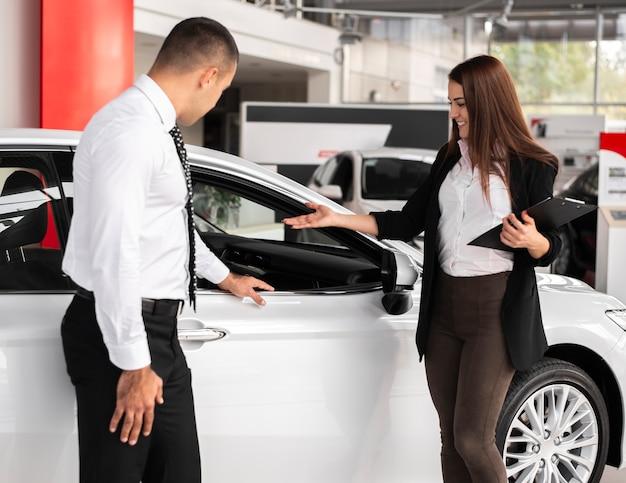 Homem e mulher em uma concessionária de carros Foto gratuita