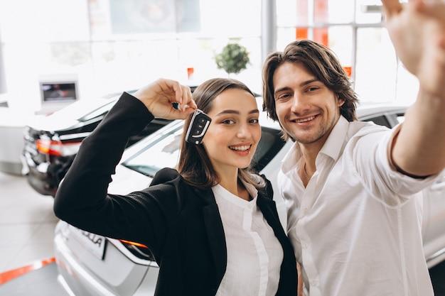 Homem e mulher escolhendo um carro em uma sala de exposições Foto gratuita