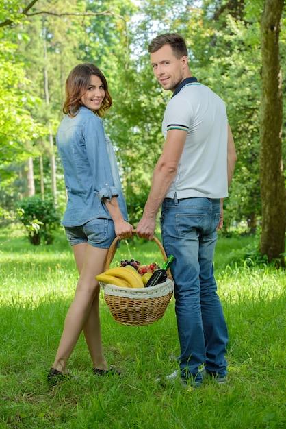 Homem e mulher estão andando no piquenique no parque. Foto Premium