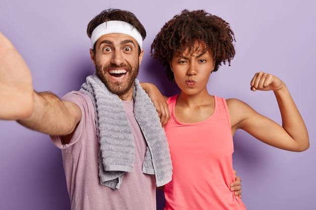 Homem e mulher felizes e diversificados tirando uma selfie, vestidos com roupas casuais, ficando próximos um do outro, praticando esportes Foto gratuita