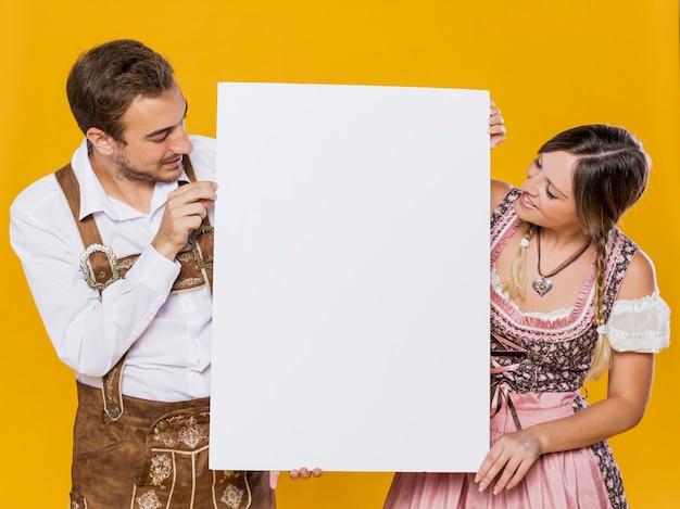 Homem e mulher festivos com maquete Foto gratuita