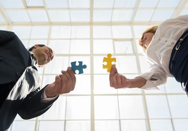 Homem e mulher, juntando peças de puzzle de quebra-cabeça. Foto Premium
