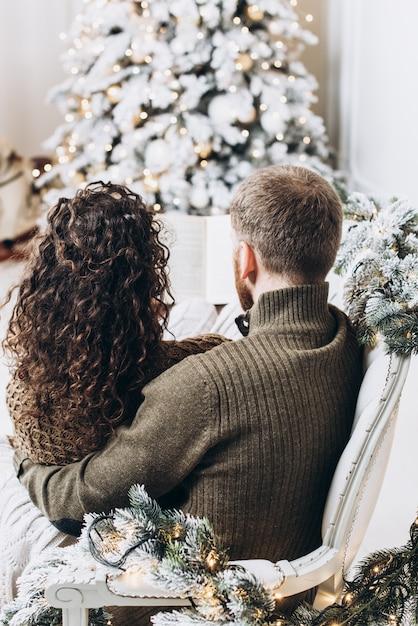 Homem e mulher lendo um livro juntos no fundo da árvore de natal Foto Premium