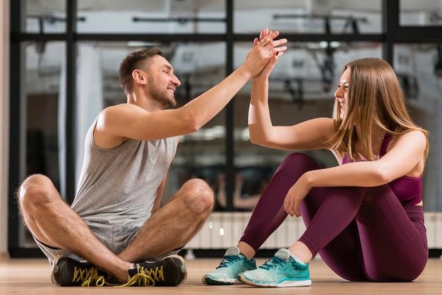 Homem e mulher orgulhosos de seus exercícios Foto gratuita