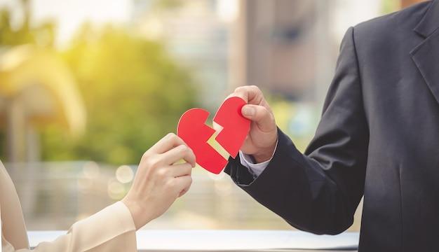 Homem e mulher que puxam um coração de papel vermelho distante. o conceito de amor não correspondido. quebrado ouvir Foto Premium