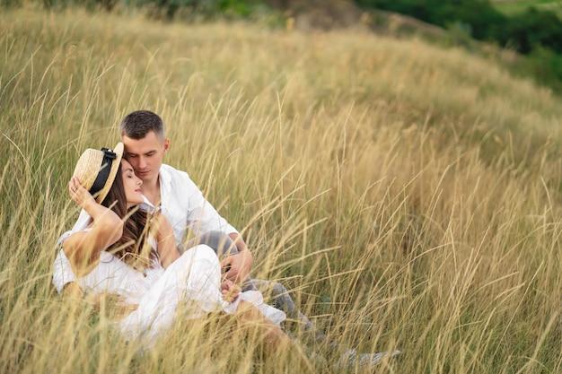 Homem e mulher relaxando juntos no campo de grama na zona rural. Foto Premium