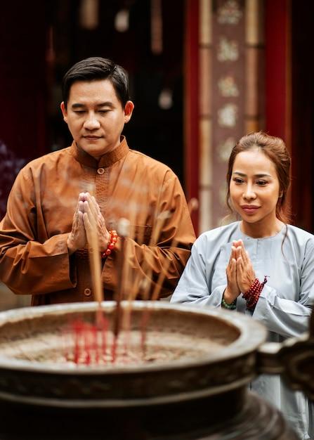 Homem e mulher rezando no templo com incenso Foto gratuita