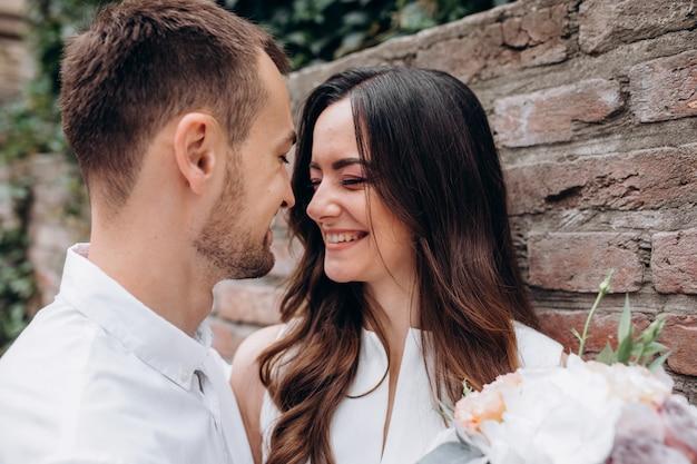 Homem e mulher se beijando concurso permanente na rua no dia do casamento Foto gratuita