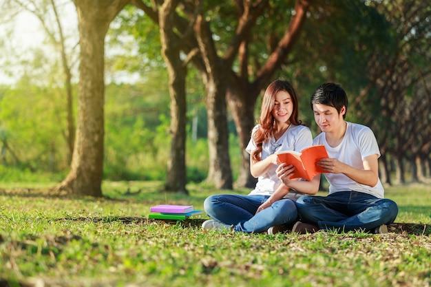 Homem e mulher sentada e lendo um livro no parque Foto Premium