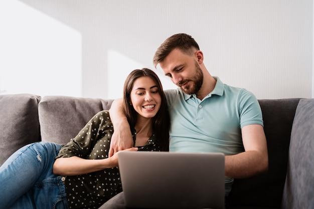 Homem e mulher sentada no sofá com um laptop Foto gratuita