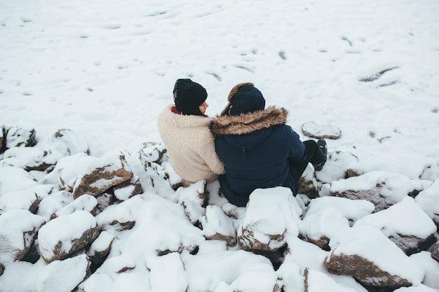 Homem e mulher sentados nas rochas cobertas de neve, na margem do lago Foto gratuita
