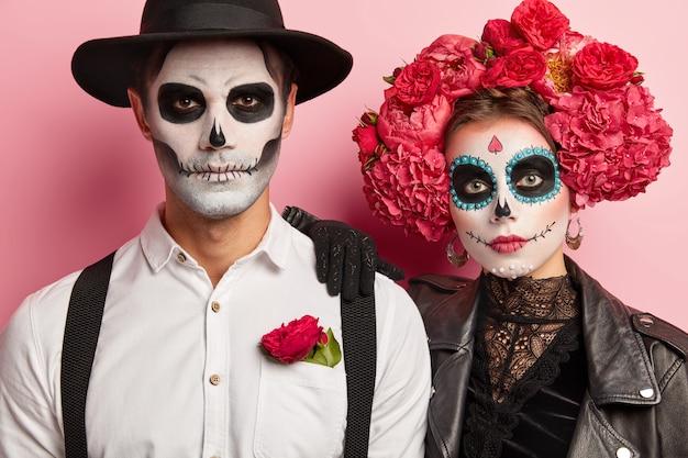 Homem e mulher sérios têm imagem tradicional mexicana, usam caveiras de açúcar, vestidas com traje especial para festa à fantasia, ficam de perto, isolado sobre fundo rosa. Foto gratuita