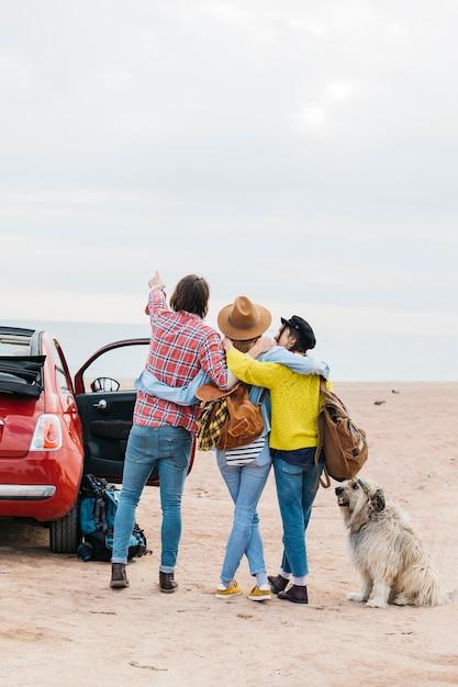 Homem, e, mulheres, abraçar, perto, car, e, cão, ligado, praia mar Foto gratuita