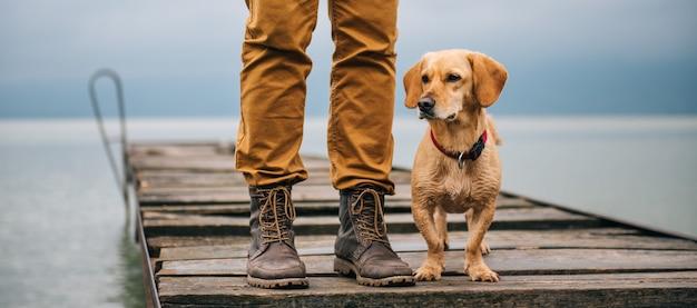 Homem e seu cachorro em pé na doca Foto Premium