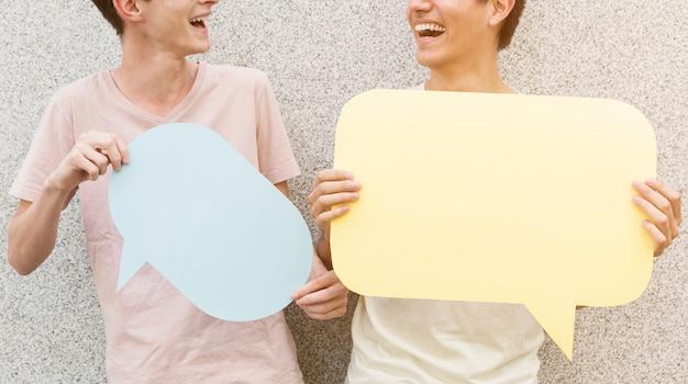 Homem e seus amigos segurando balões de fala Foto gratuita