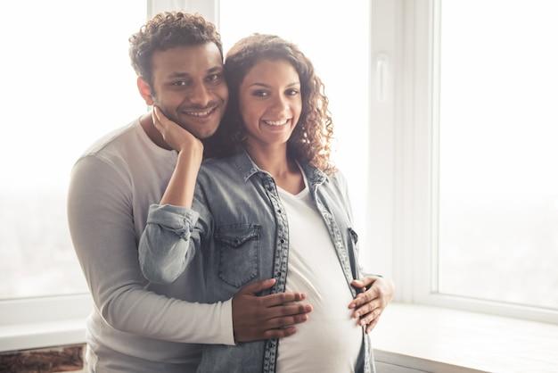 Homem e sua linda esposa grávida estão abraçando e sorrindo. Foto Premium