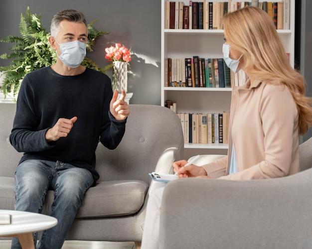Homem e terapeuta usando máscaras Foto gratuita