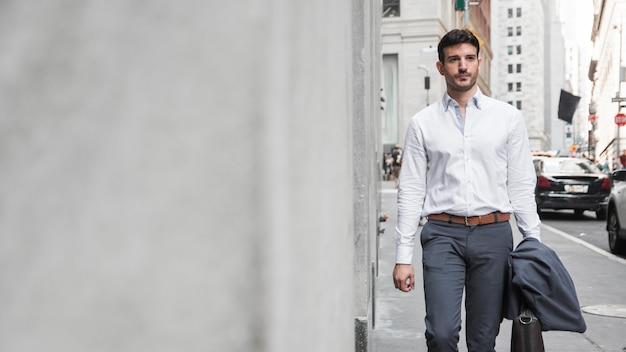 Homem elegante andando na rua Foto gratuita