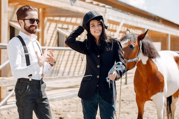 Homem elegante, ao lado de cavalo em uma fazenda com garota Foto gratuita