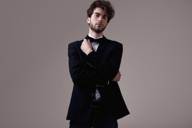 Homem elegante bonito com cabelos cacheados, vestindo smoking Foto Premium
