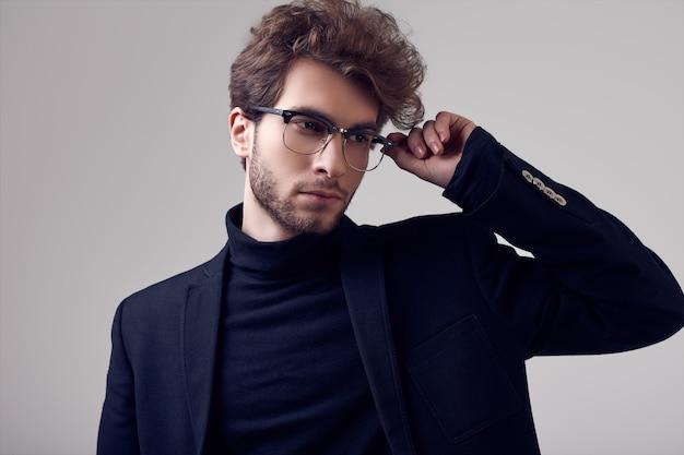 Homem elegante bonito com cabelos cacheados, vestindo terno e óculos Foto Premium