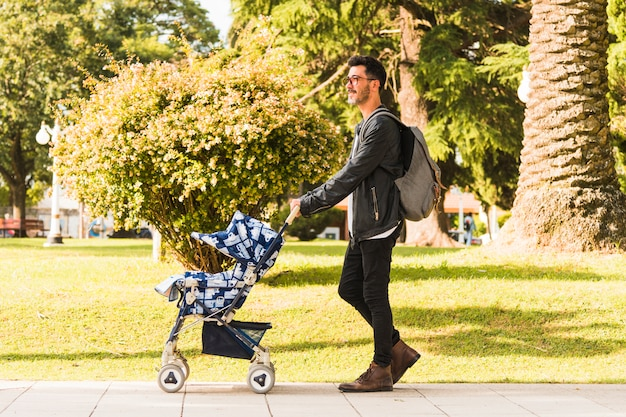 Homem elegante carregando mochila andando com carrinho de bebê no parque Foto gratuita