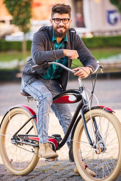 Homem elegante com óculos passeios de bicicleta. Foto Premium