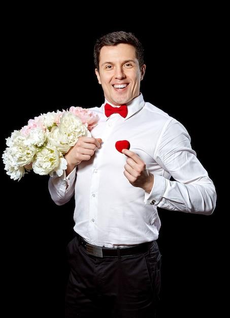 Homem elegante com um anel e flores Foto gratuita