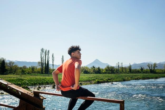 Homem elegante sentado no corrimão metálico da ponte sobre o rio Foto gratuita