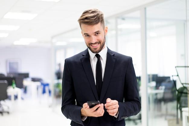 homem elegante sorrindo com um smartphone Foto gratuita