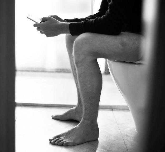 Homem, em, a, assento toalete, usando, um, smarphone Foto gratuita
