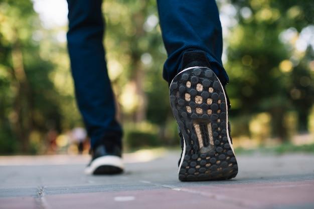 Homem em calçados esportivos, andando em um beco Foto gratuita