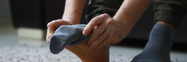 Homem em casa de manhã coloca meias cinza na perna Foto Premium