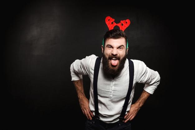 Homem em chifres de veado falso mostrando a língua sobre preto. Foto gratuita