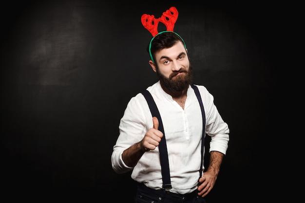Homem em chifres de veado falso mostrando bem sobre preto. Foto gratuita