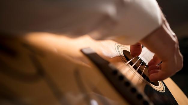 Homem em close de lado tocando guitarra Foto Premium