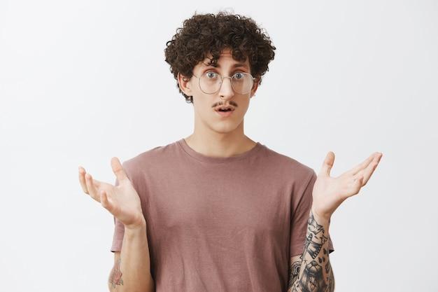 Homem em estupor, sentindo-se confuso, não consegue entender o que aconteceu em pé, com a palma da mão levantada e a boca aberta olhando sem noção e chocado, sentindo-se frustrado sobre a parede cinza Foto gratuita