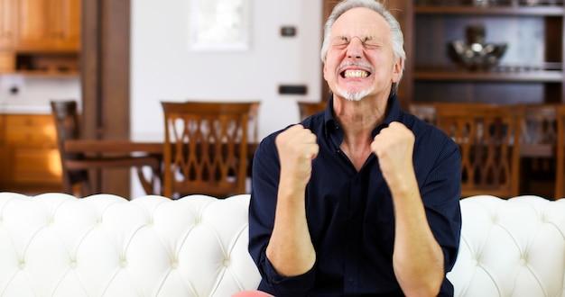Homem em êxtase exultante enquanto assistia a um jogo na tv Foto Premium