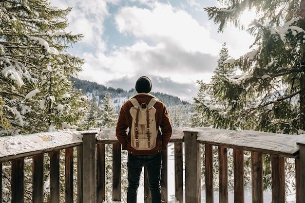 Homem em frente a cercas de madeira, cercado por colinas e florestas cobertas de neve Foto gratuita