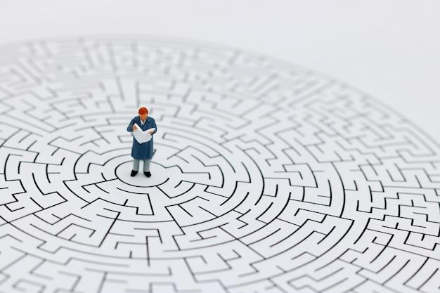 Homem em miniatura em um labirinto Foto Premium