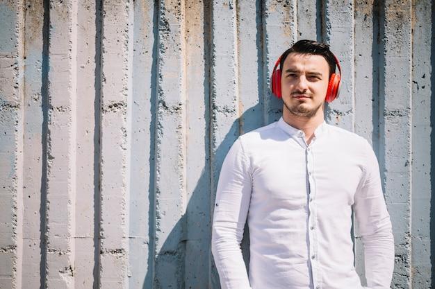 Homem em pé com fones de ouvido Foto gratuita
