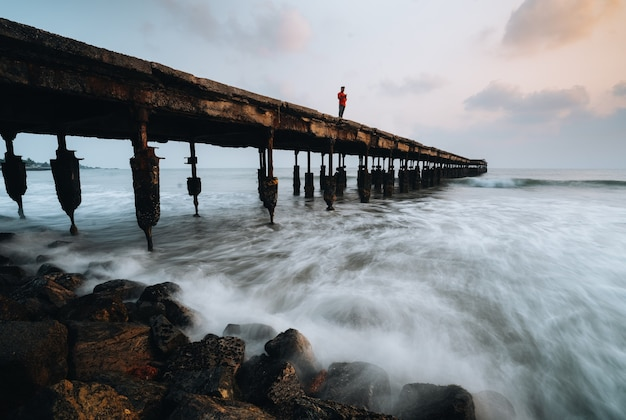 Homem em pé na ponte marítima de brocken Foto Premium