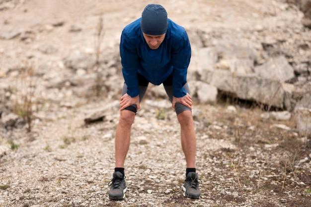 Homem em plena cena fazendo uma pausa na trilha na natureza Foto Premium