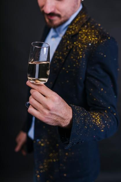 Homem, em, pó glitter, com, vidro champanha Foto gratuita