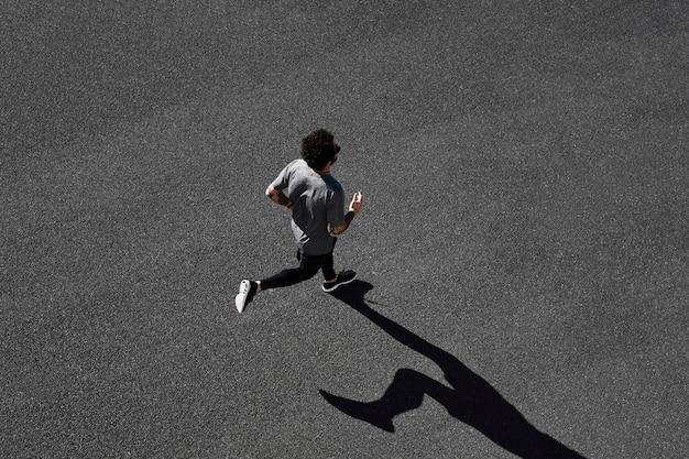 Homem em roupas esportivas correndo na estrada Foto gratuita