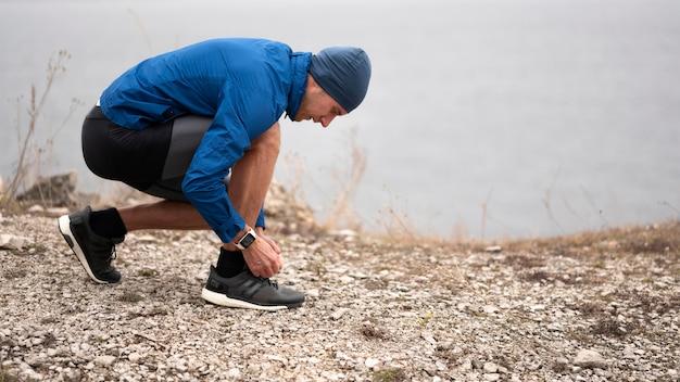 Homem em tiro certeiro amarrando os cadarços na trilha Foto Premium
